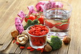 dried goji berries, water, nuts and fresh vegetables for a healthy diet