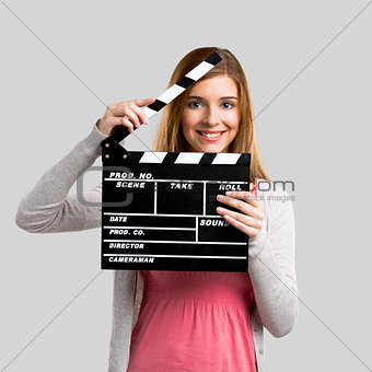 Beautiful girl holding clapboard
