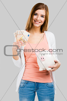 Beautiful woman putting money in a piggy bank