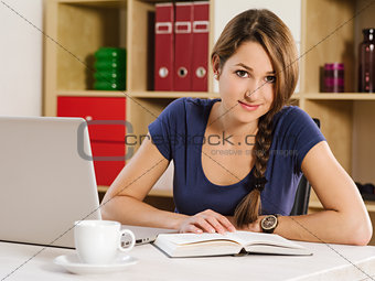Beautiful woman reading and using a laptop
