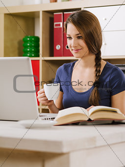 Woman smiling while using a laptop