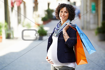 Portrait of happy and smiling pregnant woman shopping
