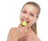 Happy young woman with making oatmeal mask with cucumber
