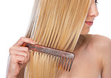 Closeup on young woman combing hair