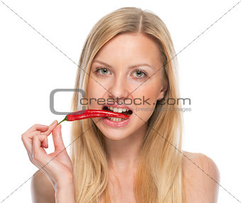Portrait of teenager eating red chili pepper