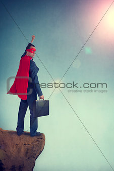 superhero businessman standing on the edge of a cliff