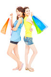 pretty young sisters standing and holding shopping bags
