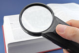 Reading a book with magnifying glass
