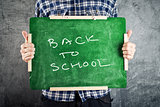 Man holding chalkboard, back to school