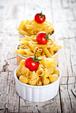 uncooked pasta and cherry tomatoes in three bowls