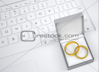 Box for jewelry with two gold rings on keyboard