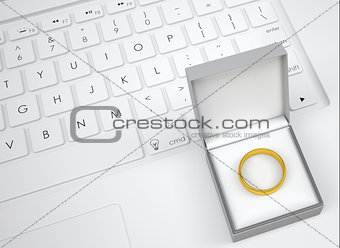Box for jewelry with gold ring on keyboard