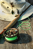 Close-up of fly-fishing reel and rod with hat