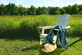 Jeans laying on adirondack chair in field