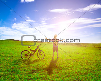 backpacker standing next to bicycle with sunrise background