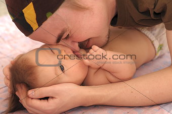 Daddy playing with newborn baby