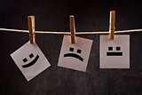Emoticons on note paper attached to rope with clothes pins
