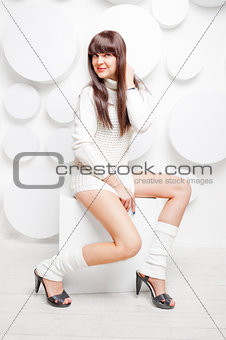 smiling brunette in a sweater on a cube