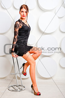 charming girl in a chair in lace dress