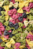 Multicolor uncooked farfalle pasta background