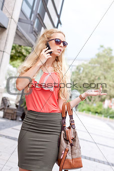 attractive young blonde woman talking on the phone outdoor