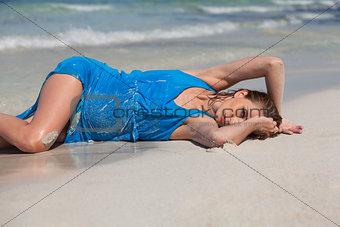 attractive young woman in blue dress on the beach