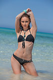attractive woman in black bikini on the beach summertime