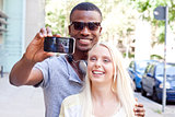 young smiling multiracial couple taking foto by smartphone