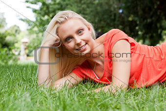beautiful young blonde girl lying in grass summertime