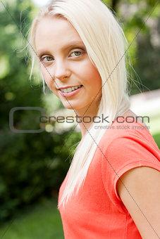 beautiful young blonde girl lying in grass summertime
