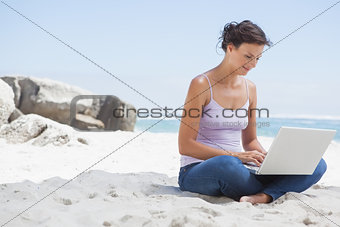Pretty brunette using laptop on the beach