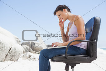 Pretty brunette using laptop on the beach sitting on swivel chair