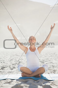 Peaceful woman sitting in lotus pose on beach