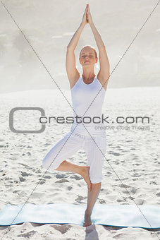 Calm woman standing in tree pose on beach