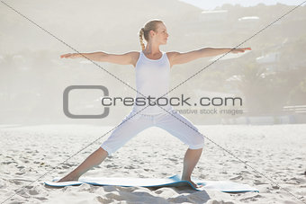 Calm woman standing in warrior pose on beach