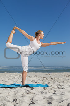 Blonde woman standing in warrior pose on beach
