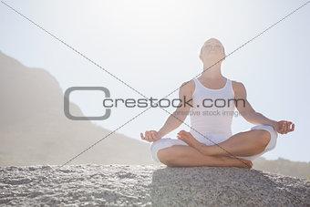 Blonde woman sitting in lotus pose on beach