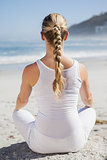 Blonde woman sitting in lotus pose on beach