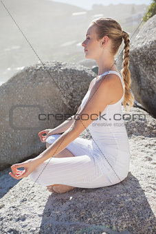Blonde woman sitting in lotus pose on a rock