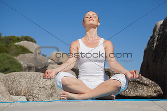 Blonde woman sitting in lotus pose on beach on mat