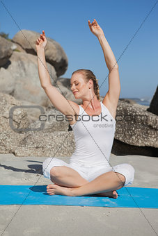 Blonde woman sitting in lotus pose on beach on mat with arms raised