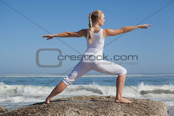 Blonde woman standing in warrior pose on beach on rock