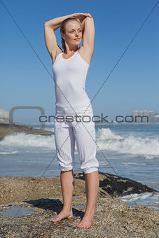 Blonde woman standing on rock stretching arms