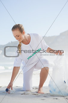 Blonde volunteer picking up trash on the beach