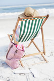 Woman in sunhat sitting on beach in deck chair