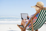 Woman in sunhat sitting on beach in deck chair using tablet pc