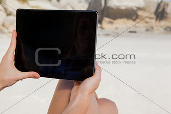 Woman sitting on beach using tablet pc