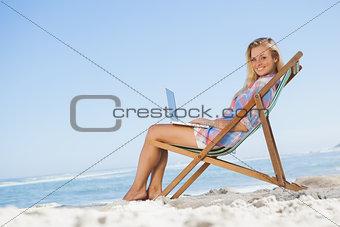 Blonde sitting on beach using her laptop smiling at camera