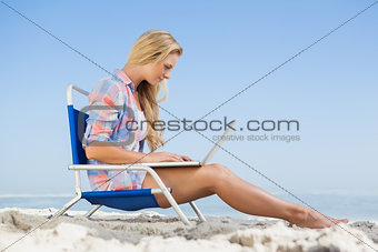 Pretty blonde sitting on beach using her laptop