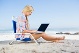 Woman sitting on beach using her laptop